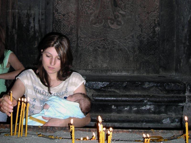 Kvinde med barn i Geghart kirken i Armenien - Globetrotters