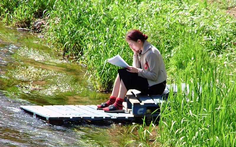 Kvinde læser ved Vilnius-floden i Vilnius.