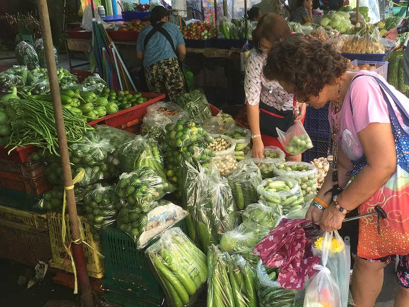 Damer på Pak Klong Talat-markedet i Bangkok